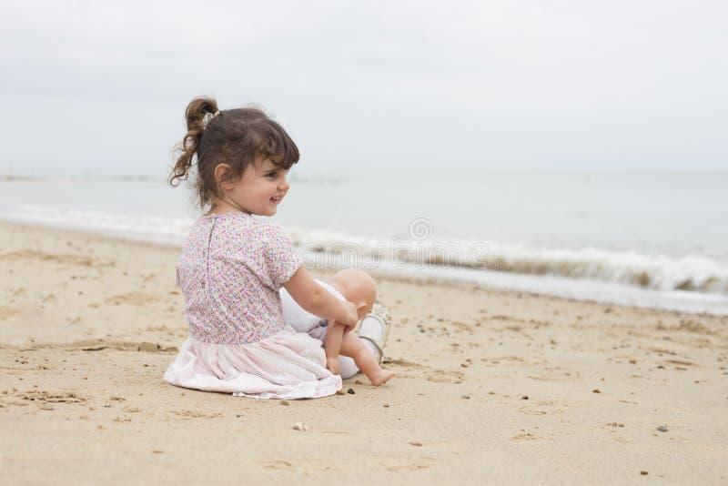 Meisje met haar dolly op het strand royalty-vrije stock foto's
