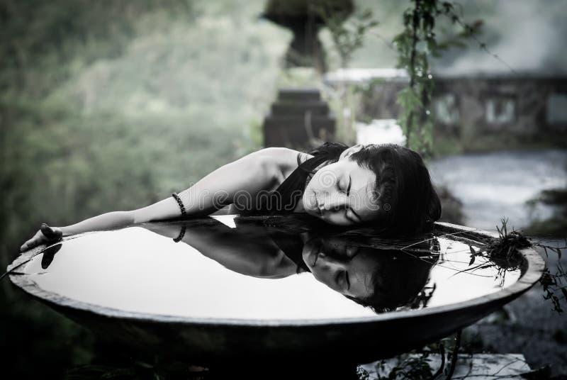 Meisje met haar gedachtengang in grote kom in het mystieke verlaten hotel in Bali indonesië stock foto