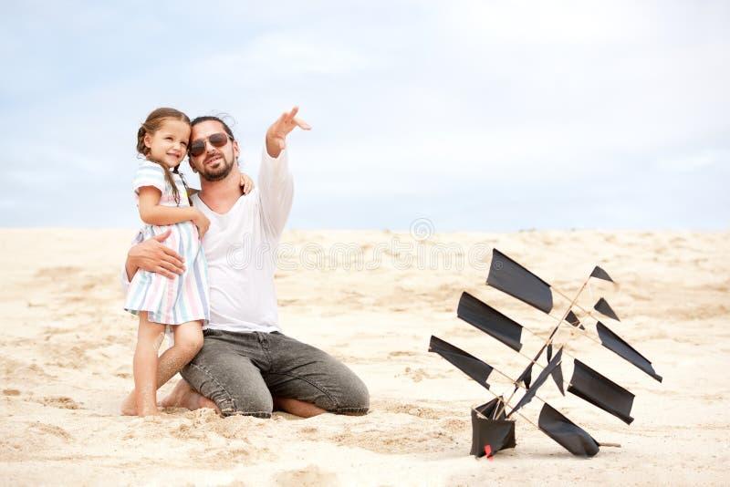Meisje met haar gelukkige de kustoceaan van de vader vliegende vlieger stock foto
