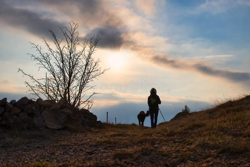 Meisje met haar hond in de bergweg op een godsdienstige bedevaart stock afbeelding