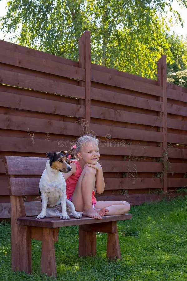Meisje met haar hondzitting op houten bank royalty-vrije stock afbeeldingen