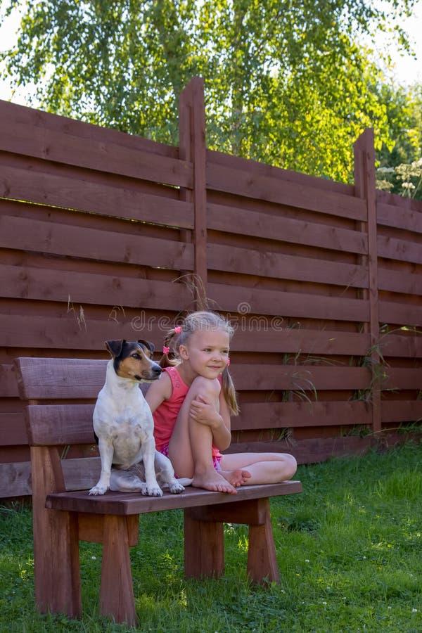 Meisje met haar hondzitting op houten bank stock afbeelding