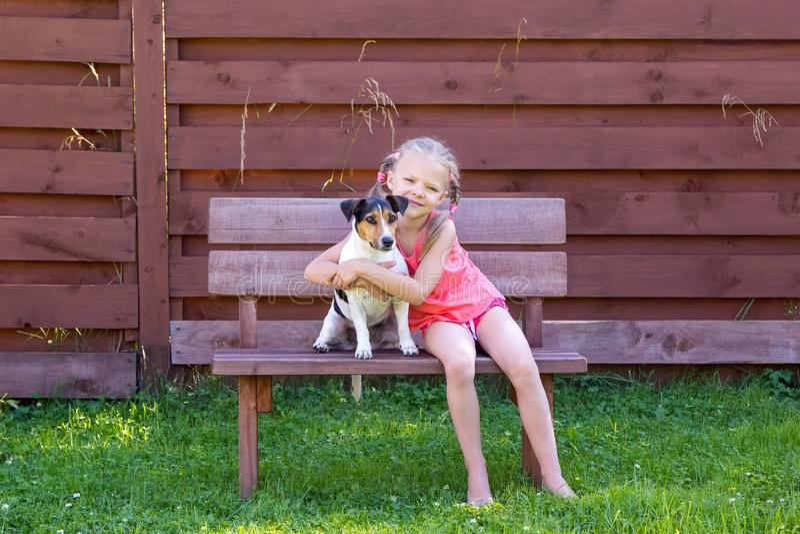Meisje met haar hondzitting op houten bank royalty-vrije stock afbeelding