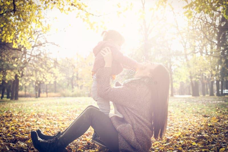Meisje met haar moeder die in park spelen stock foto