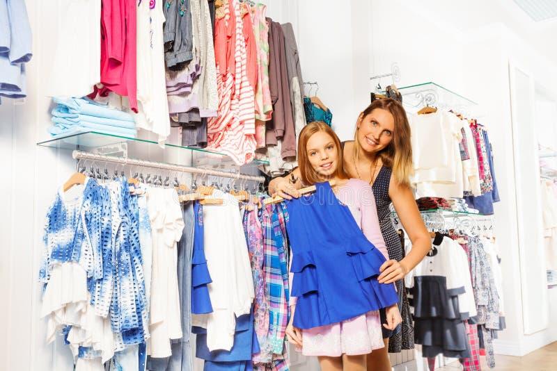 Meisje met haar moeder het winkelen en greep gekozen punt stock fotografie