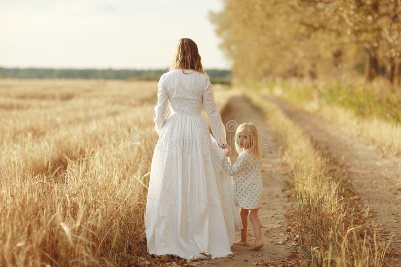 Meisje met haar moeder op de herfstgebied stock fotografie