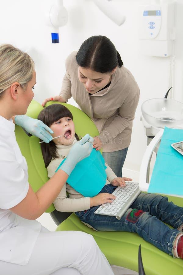 Meisje met haar moeder op het kantoor van de tandarts stock fotografie