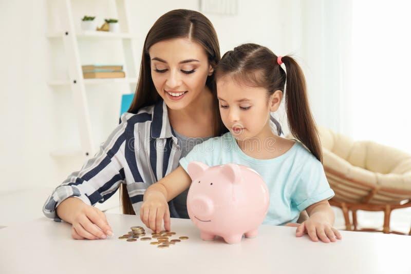 Meisje met haar moederzitting bij lijst en binnen het zetten van muntstukken in spaarvarken De besparingenconcept van het geld stock fotografie
