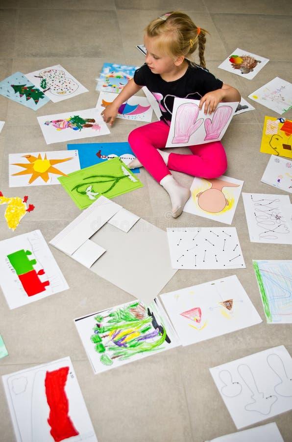 Meisje met haar tekeningen op de vloer stock afbeeldingen