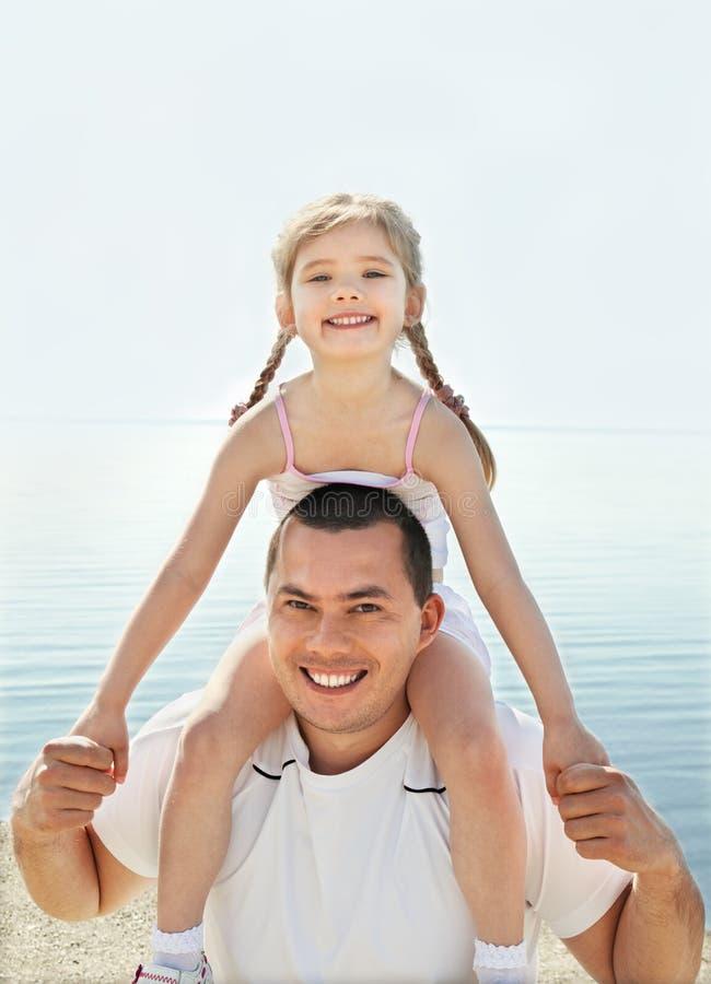Meisje met haar vader die pret op strandvakantie hebben stock afbeeldingen