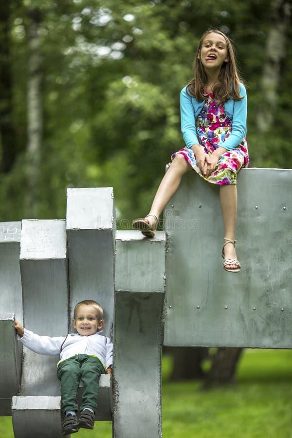 Meisje met haar weinig broer op de Speelplaats in stadspark royalty-vrije stock foto's