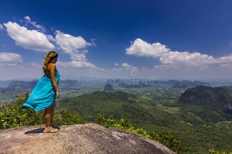 Meisje met handen die op rots bij zonsondergang met hieronder bergen opstaan royalty-vrije stock afbeeldingen