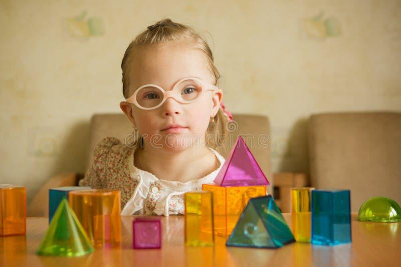 Meisje met het Benedensyndroom spelen met geometrische vormen stock foto