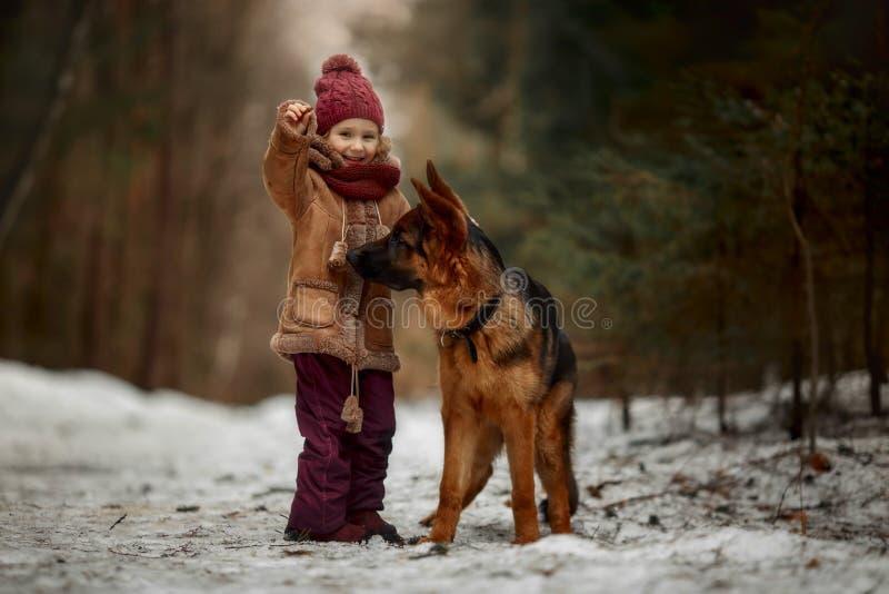 Meisje met het puppy van de Duitse herder 6de maanden bij de vroege lente royalty-vrije stock fotografie