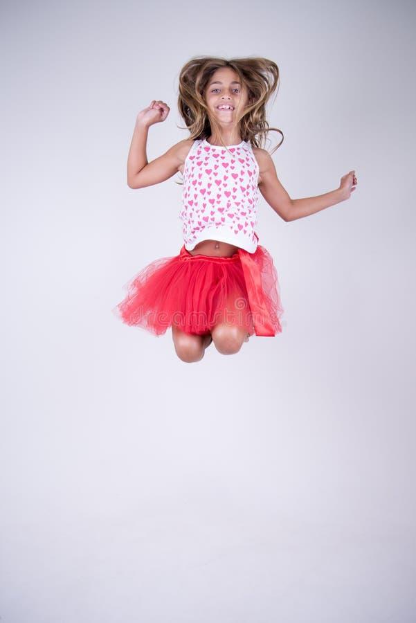 Meisje met het rode rok gelukkig springen en het glimlachen met handen omhoog en haar in de wind stock foto
