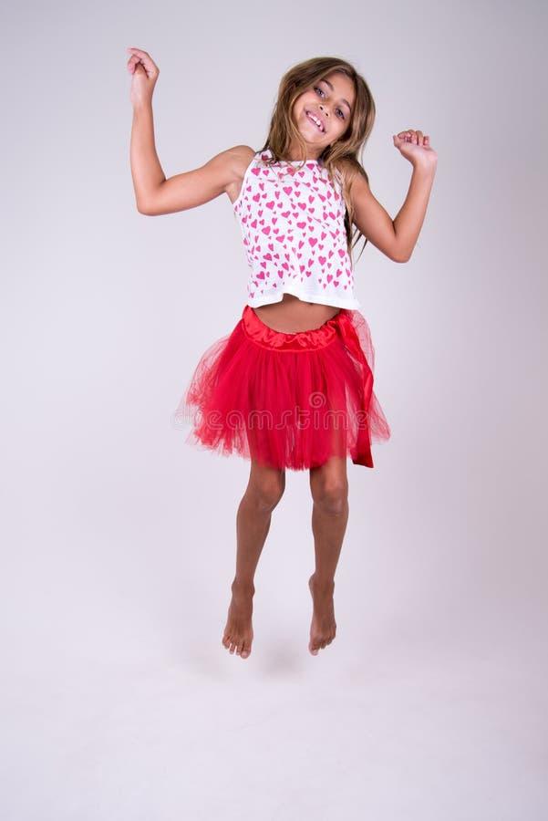 Meisje met het rode rok springen gelukkig met omhoog handen royalty-vrije stock afbeelding