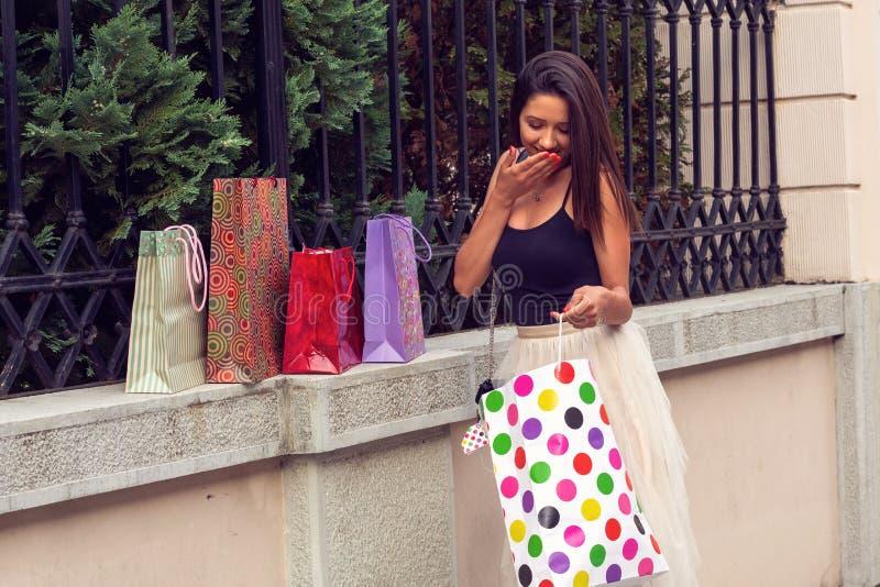 Meisje met het winkelen zakken gekochte kleren en schoenen stock afbeeldingen
