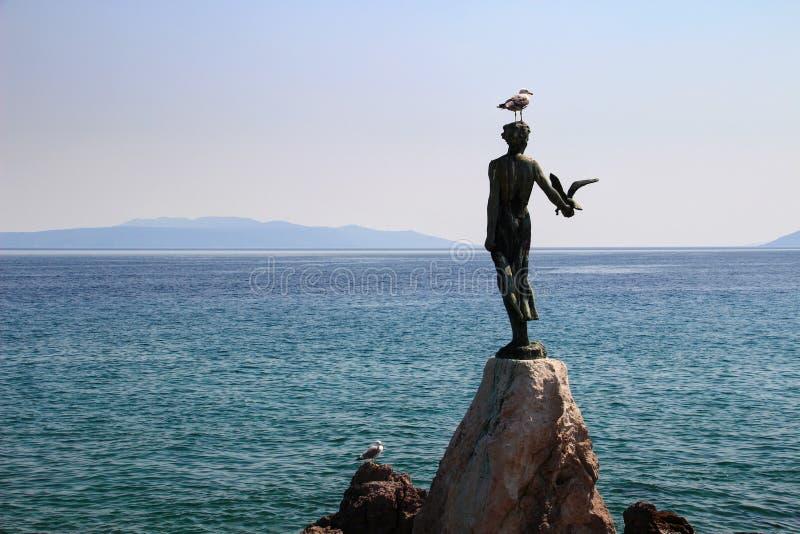Meisje met het zeemeeuwstandbeeld en het Adriatische Overzees Opatija Kroatië stock fotografie