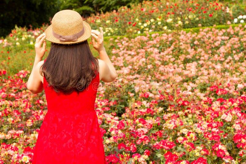 Meisje met hoed in roze tuin royalty-vrije stock afbeeldingen