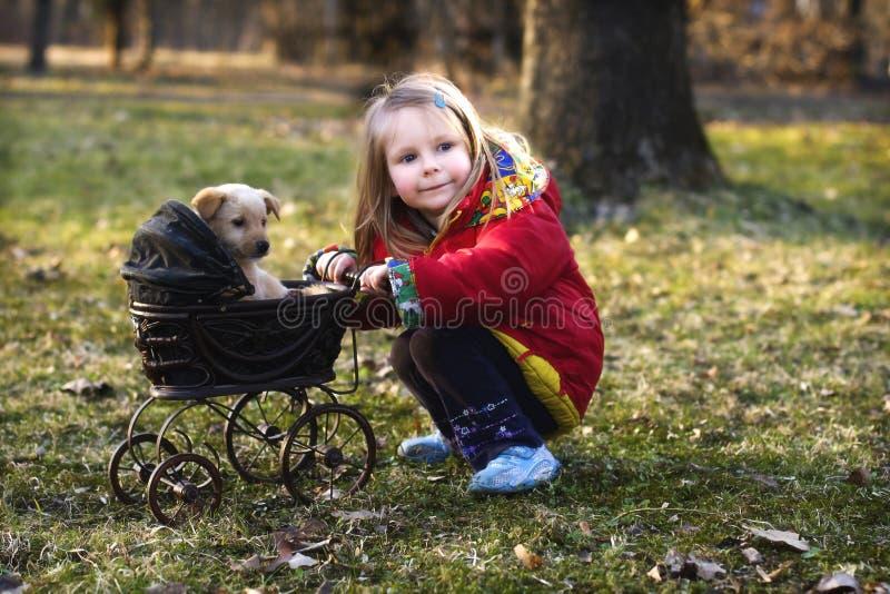 Meisje met hond en kinderwagen   stock afbeelding