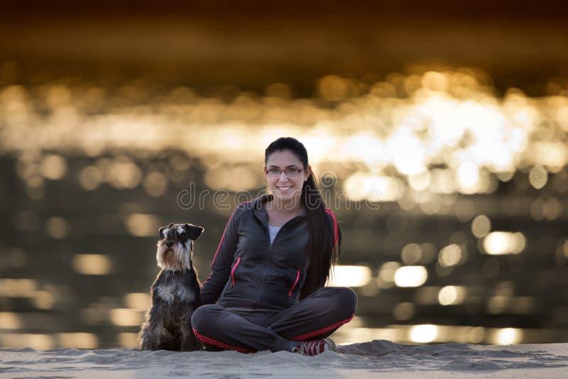 Meisje met hond op zandige kust royalty-vrije stock afbeeldingen