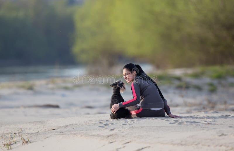 Meisje met hond op zandige kust stock fotografie