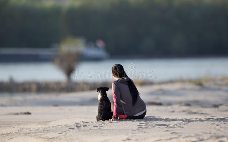 Meisje met hond op zandige kust stock afbeeldingen