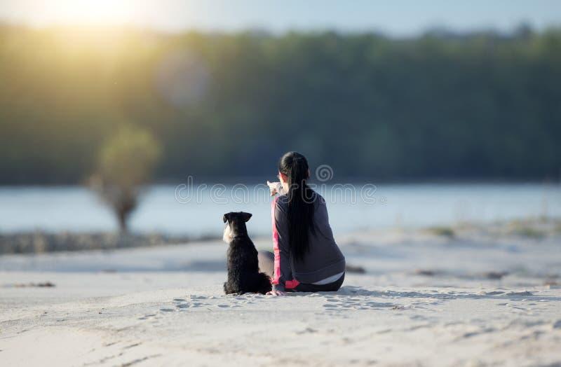 Meisje met hond op zandige kust royalty-vrije stock foto