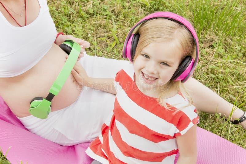 Meisje met hoofdtelefoons en een zwanger mamma royalty-vrije stock afbeeldingen