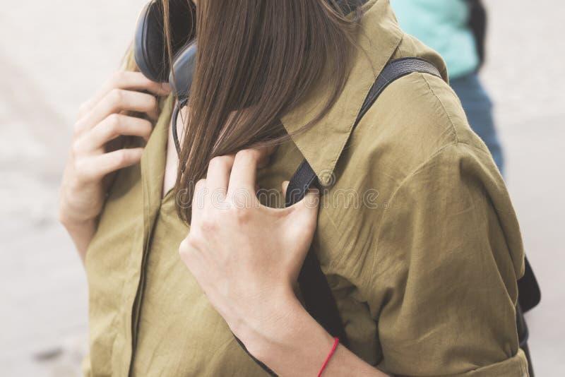 Meisje met hoofdtelefoons in groen overhemd stock fotografie