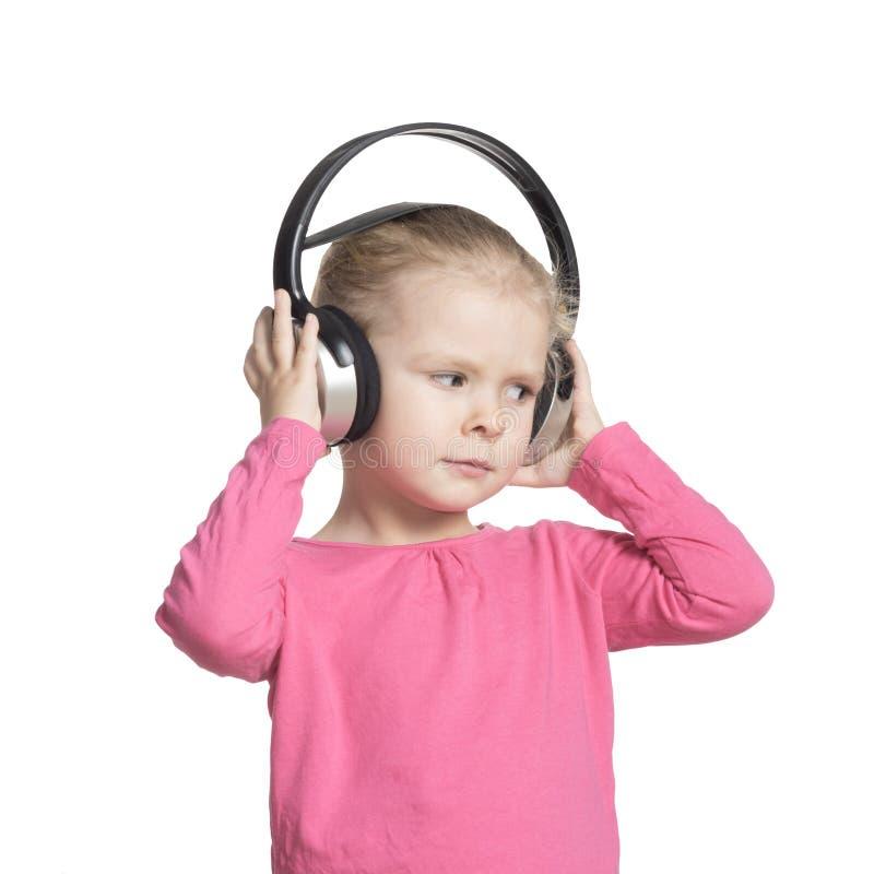 Meisje met hoofdtelefoons, op witte achtergrond Het kind luistert aan muziek isoleer royalty-vrije stock foto's