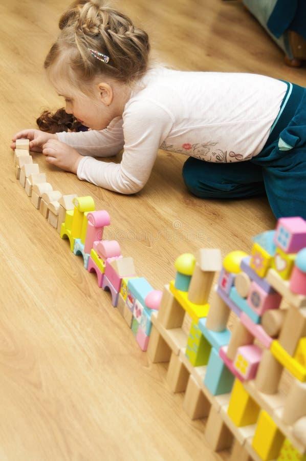 Meisje met houten stuk speelgoed blokken royalty-vrije stock afbeeldingen