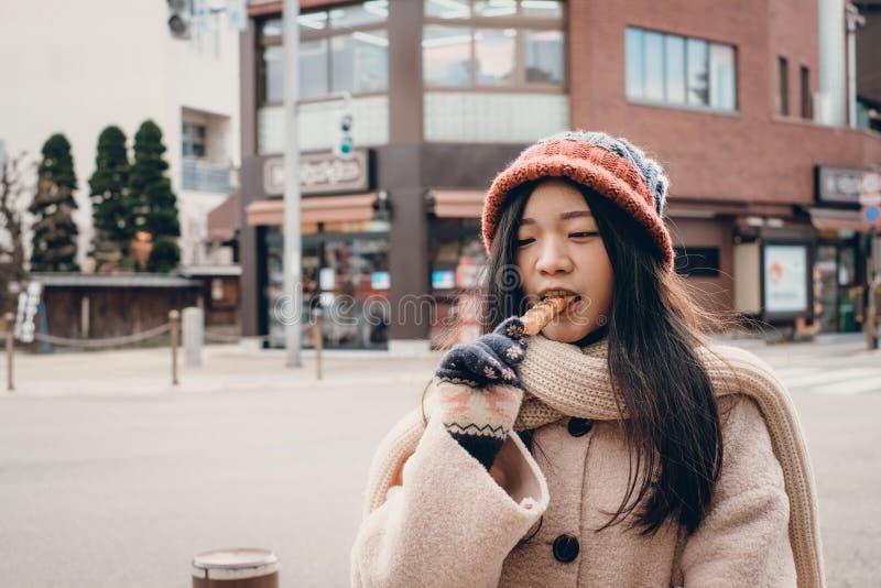 Meisje met Japanse snacknaam Kibi Dango stock fotografie
