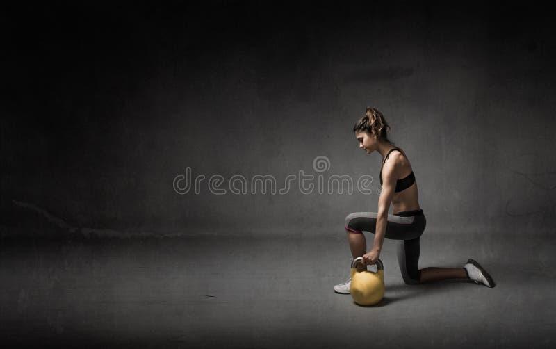 Meisje met kettlebell op hand royalty-vrije stock afbeeldingen