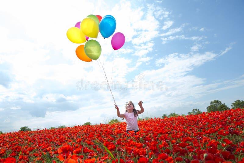 Meisje met kleurrijke ballons die in blauwe zonnige hemel vliegen stock fotografie