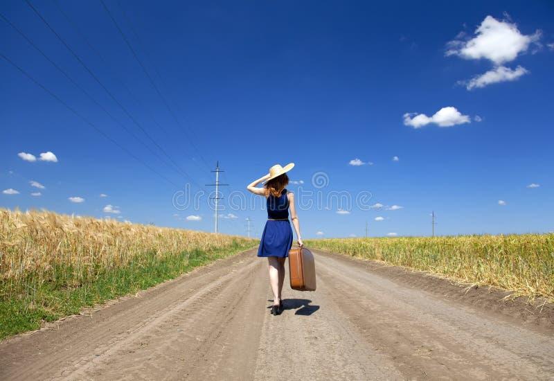Meisje met koffer bij landweg. stock fotografie