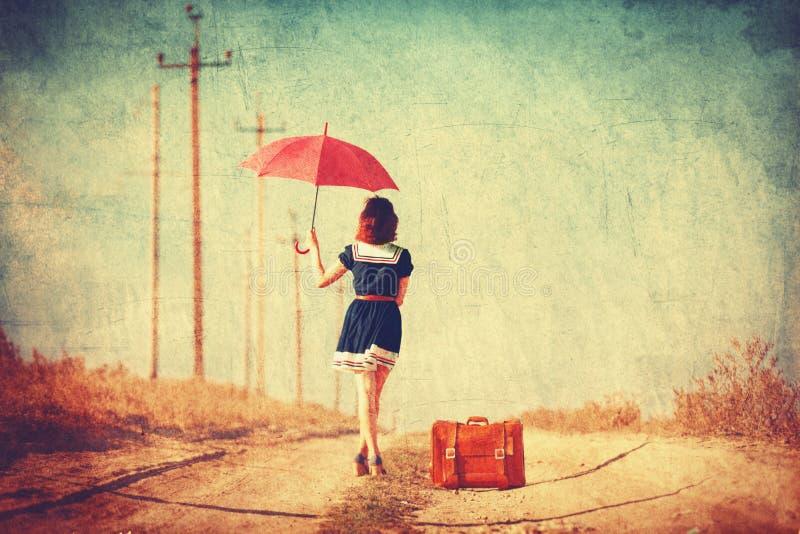 Meisje met Koffer op de Weg stock foto