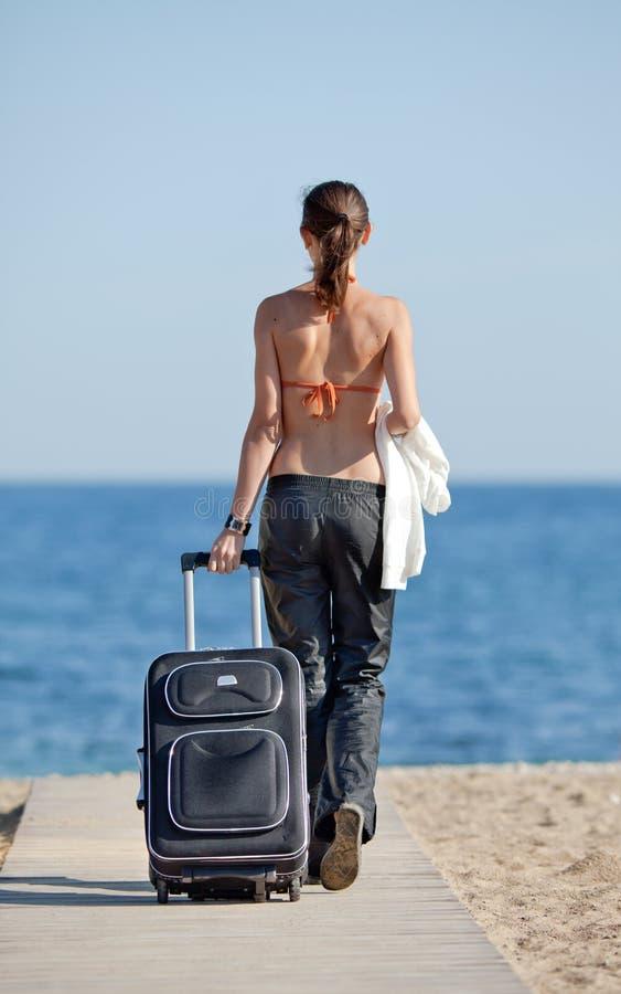 Meisje met koffer op het strand stock foto