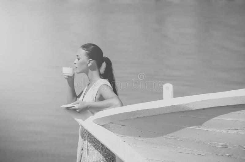 Meisje met koffiekop bij boot royalty-vrije stock foto