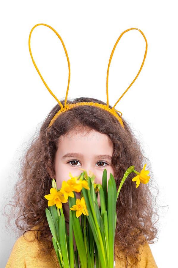 Meisje met konijntjesoren met bloemen op een lichte achtergrond stock foto