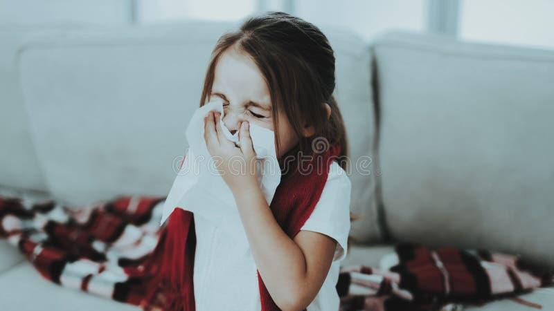 Meisje met Koude Zitting op Bank in Rode Sjaal Ziek jong meisje Witte bank in ruimte Ongelukkig kind ziekteconcept stock afbeeldingen