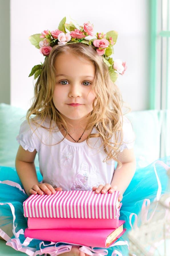 Meisje met kroon en roze boeken stock foto