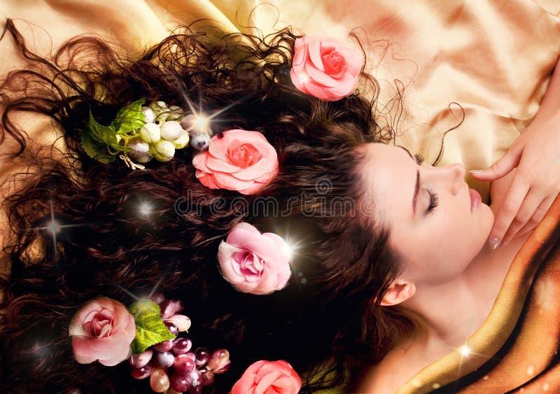 Meisje met lang gezond haar dat met bloemen wordt verfraaid. royalty-vrije stock afbeelding