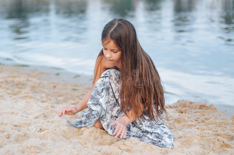 Meisje met lang haar in de zomerkleding het spelen met zand op het strand stock afbeelding