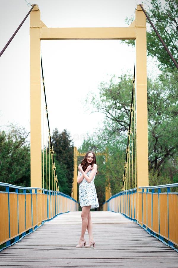 Meisje met lang haar en krullen in een kleding die zich bij de opschorting bevinden stock foto's