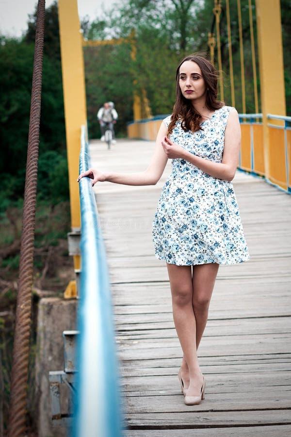 Meisje met lang haar en krullen in een kleding die zich bij de opschorting bevinden stock fotografie