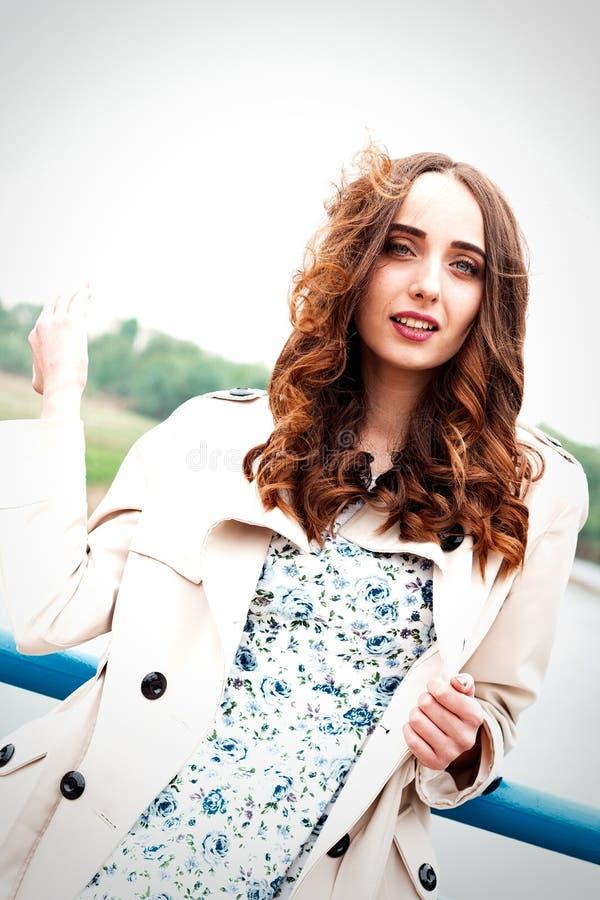 Meisje met lange haar en krullen in een kleding en laag die zich op su bevinden royalty-vrije stock afbeelding