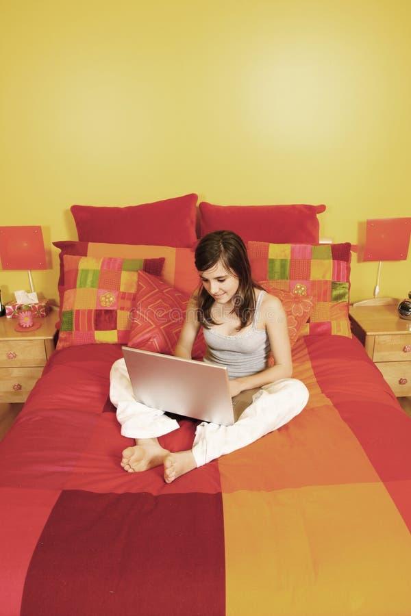Meisje met laptop in bed royalty-vrije stock foto