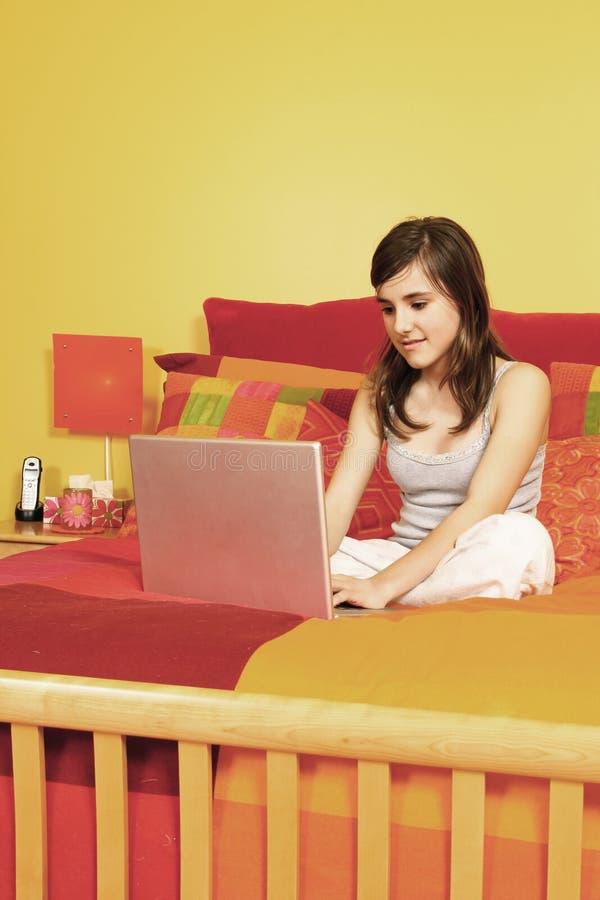 Meisje met laptop in bed stock afbeelding
