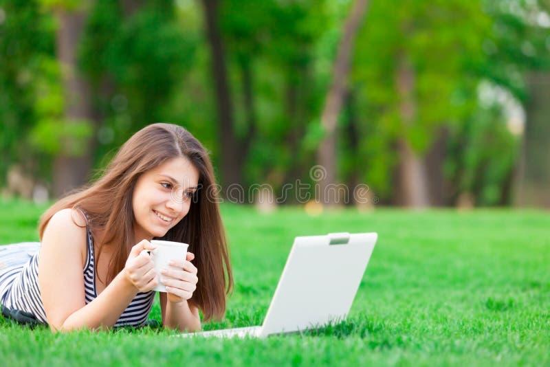 Meisje met laptop computer en kop stock fotografie